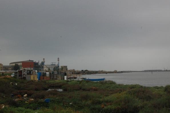Cagliari, S. Gilla, , presenza di baracche in metallo, legname ed eternit. Sullo sfondo la centrale ENEL