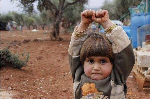 campo profughi di Atmeh (Siria), Hudea, 4 anni, si arrende al fotografo Osman Sagirli, avendo scambiato l'obiettivo per la canna di un fucile